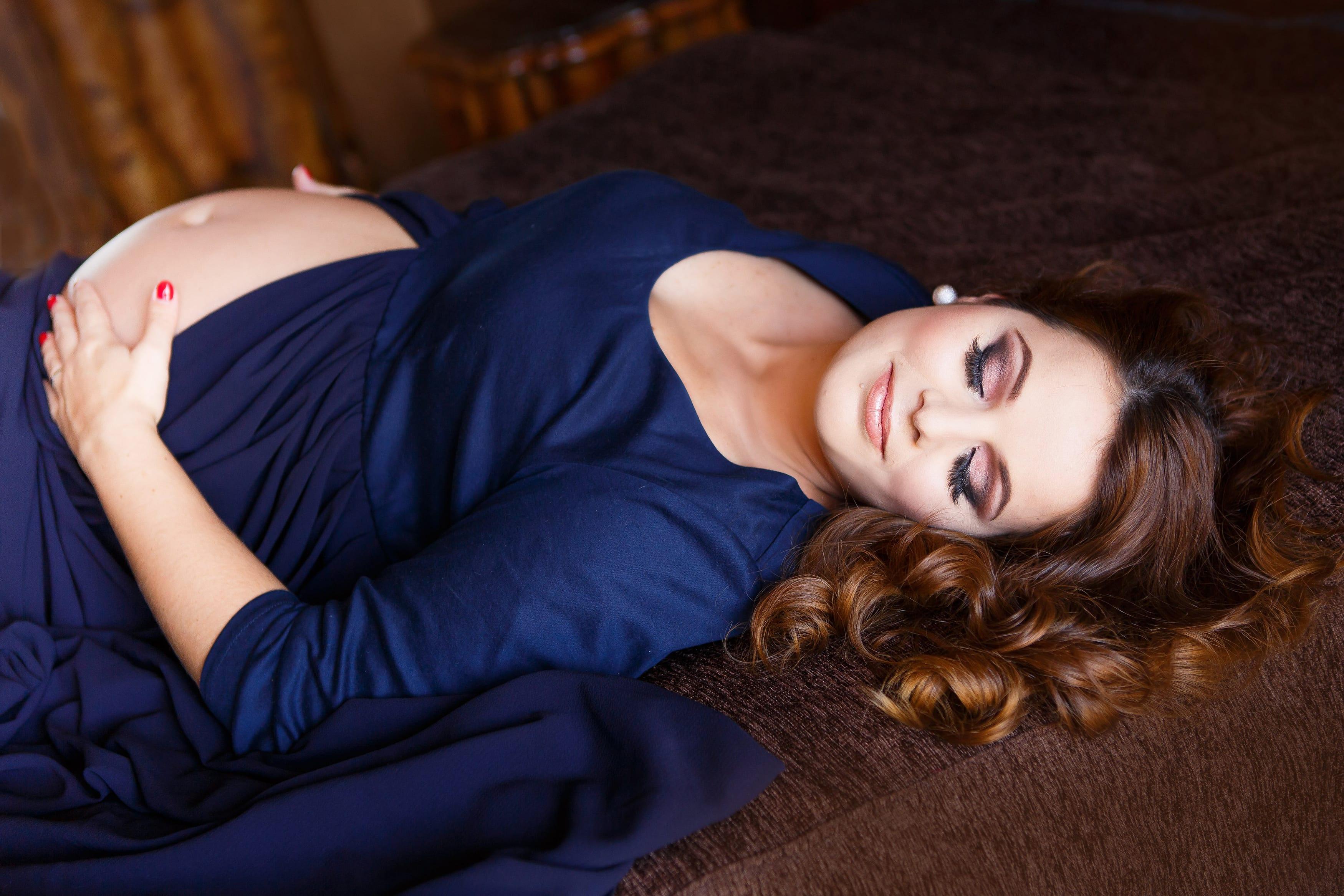 Frau schwanger liegt auf einem Bett Fotoshooting in Berlin von Donna Bellini