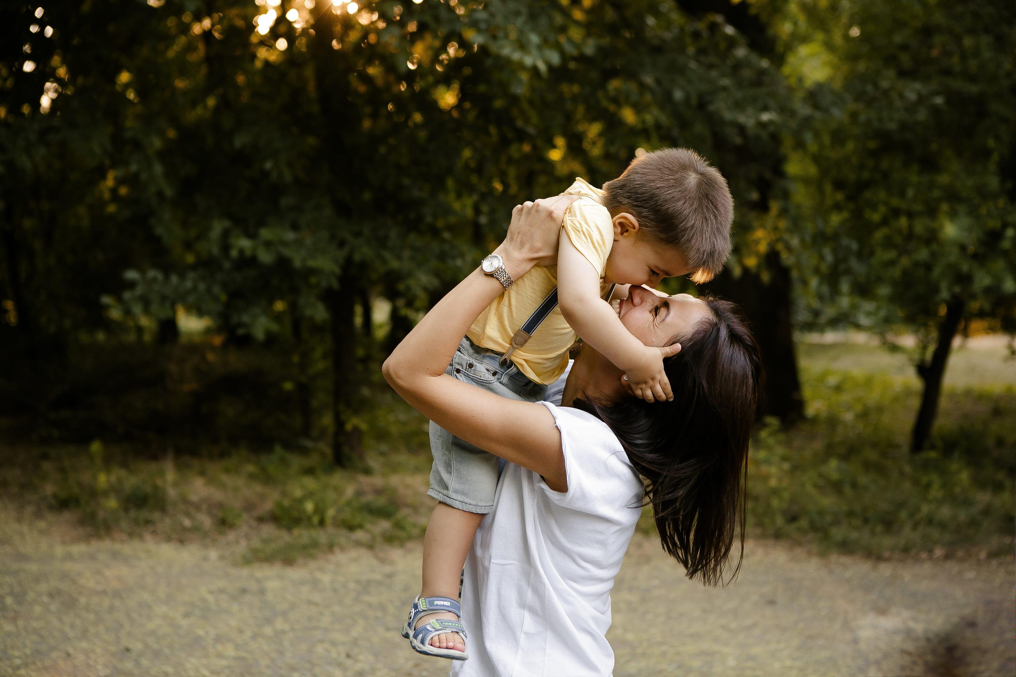 Kind mit Mutter im Arm draussen Fotografie