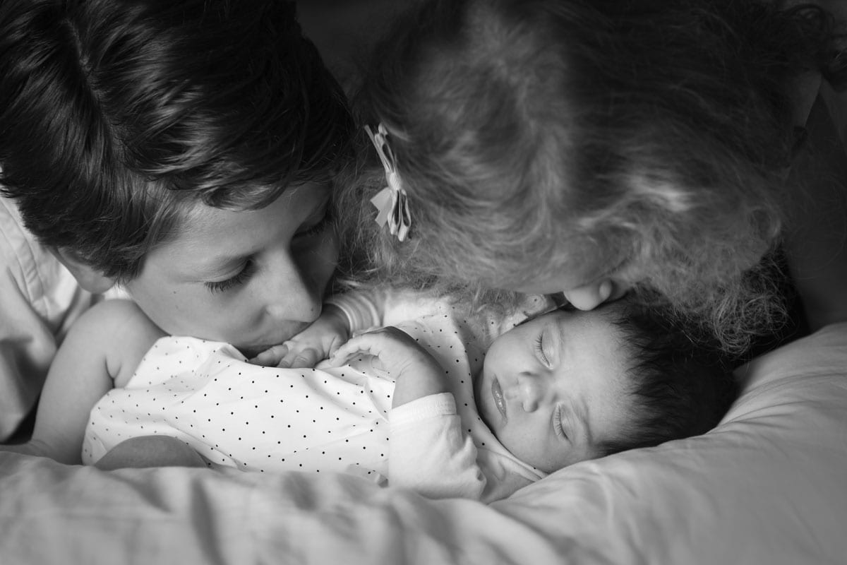 Bruder und Schwester kuessen ein neugeborenes Baby waehrend eines neugeborenen Fotoshootings im Donna Bellini Photo Studio Berlin