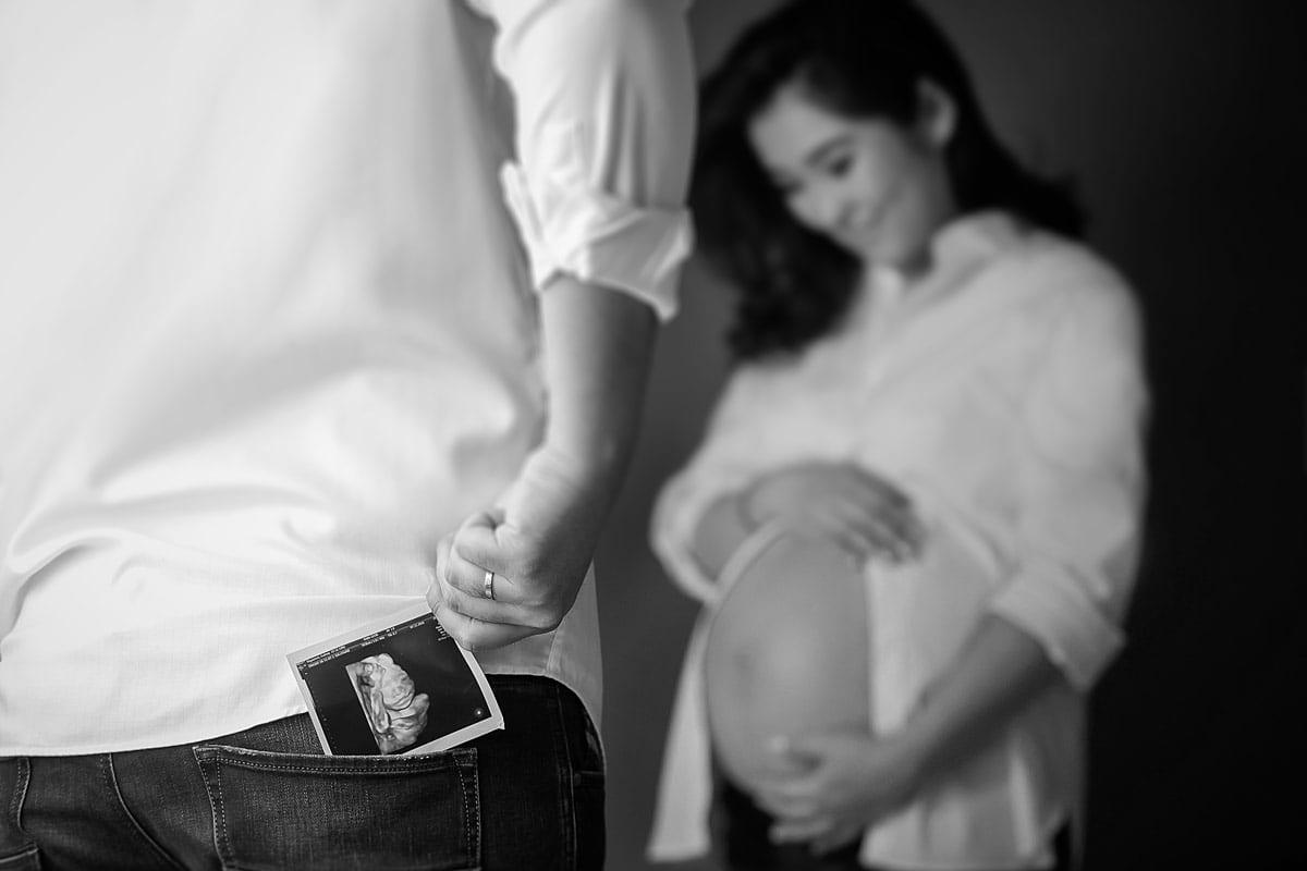Die schwangere Dame zeigt ihren Babybauch mit dem Partner im Vordergrund waehrend des Babybauch Fotoshootings von Donna Bellini Berlin