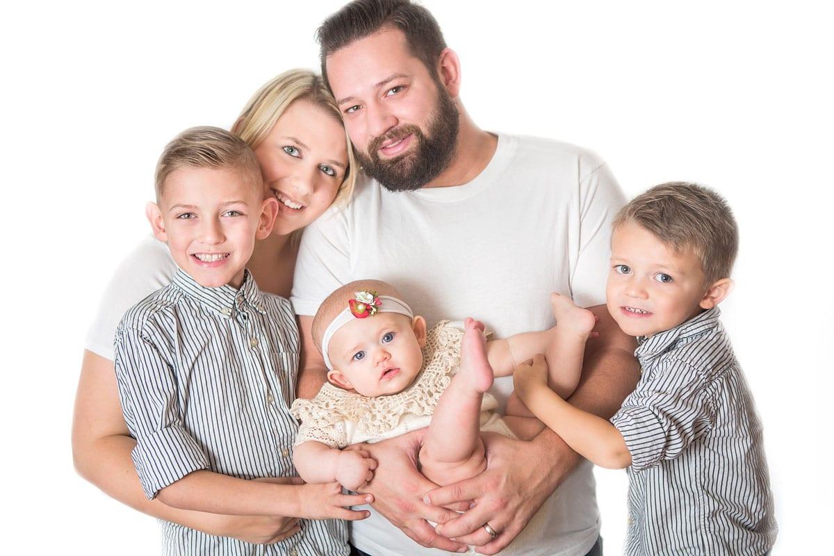 Familie mit Mutter Vater und zwei Kindern und einem kleinen Baby posiert waehrend eines Familienfotos von Donna Bellini Photo Studio Berlin