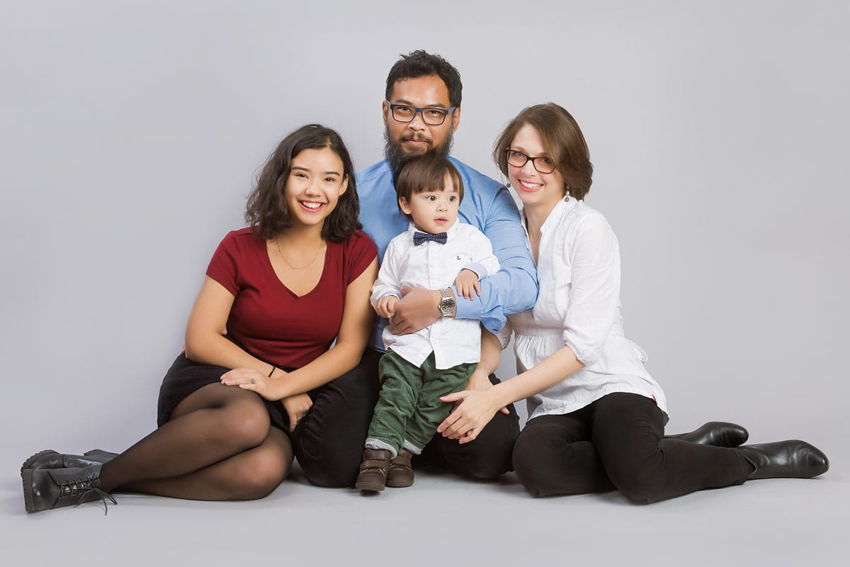 Familie mit zwei Kindern sitzten auf dem Boden und posieren waehrend eines Familienfotos von Donna Bellini Photo Studio Berlin