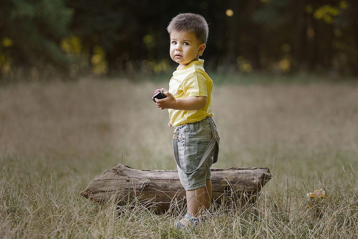 Kleiner Junge bleibt auf Gras und schaut in die Kamera waehrend des Outdoor-Fotoshootings von Donna Bellini Photo Studio Berlin