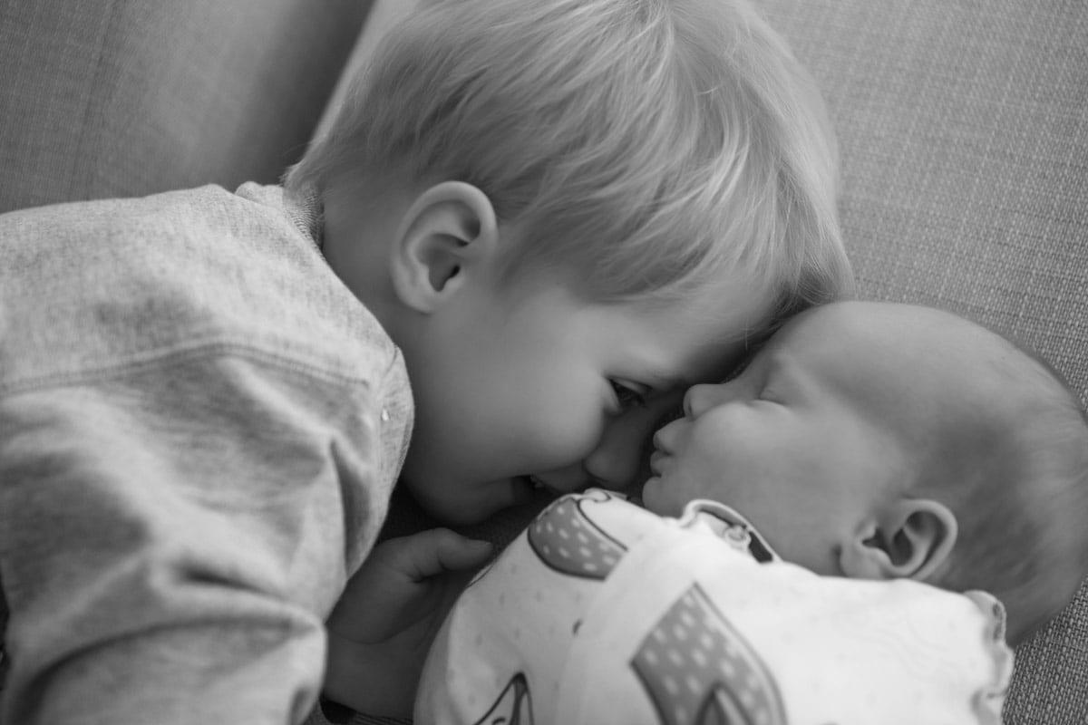 Kleiner Junge kuesst neugeborenes waehrend eines neugeborenen Fotoshootings in Donna Bellini Photo Studio Berlin