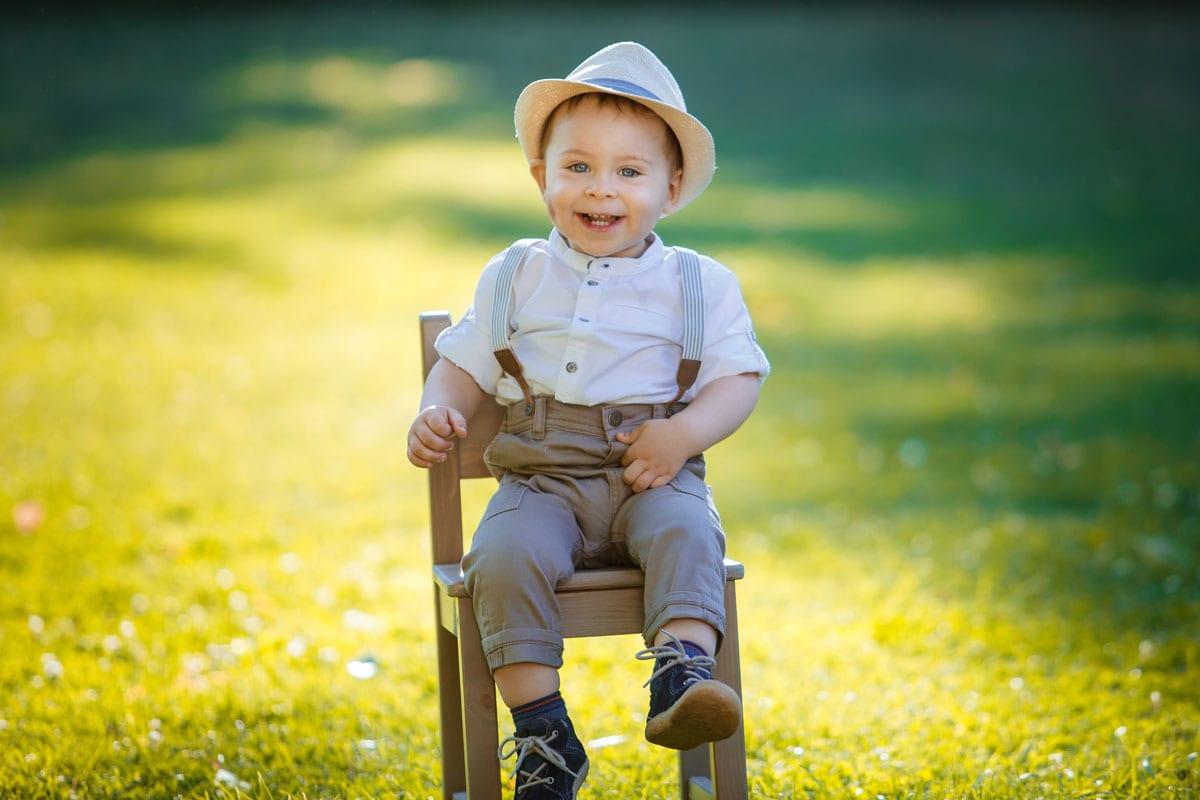 Kleiner Junge sitzt auf einem Stuhl und laechelt in der Kamera waehrend des Outdoor-Fotoshooting mit Donna Bellini Photo Studio Berlin