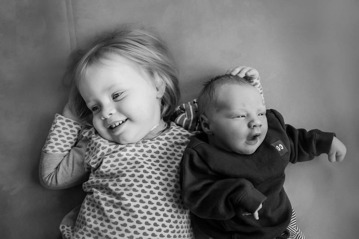 Kleines Maedchen und Neugeborenes lag waehrend eines neugeborenen Fotoshootings im Donna Bellini Photo Studio Berlin auf dem Boden