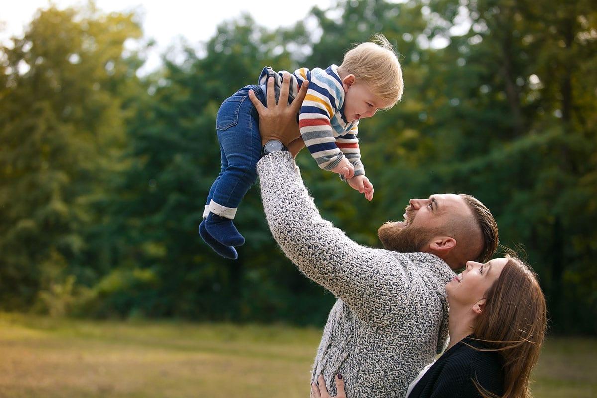 Mann haelt seinen Sohn hoch in die Luft und Mutter schaut sie beim Outdoor-Fotoshooting von Donna Bellini Photo Studio Berlin an