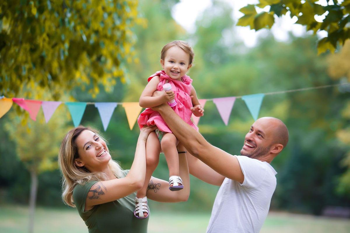Mann und Frau halten ihre Tochter beim Outdoor-Fotoshooting mit Donna Bellini Photo Studio Berlin hoch in der Luft