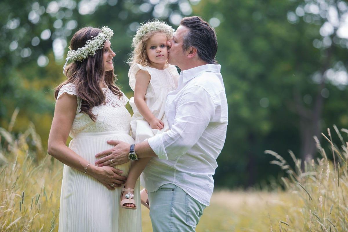 Mann und schwangere Frau im weissen Kleid halten ihre kleine Tochter beim Outdoor-Fotoshooting mit Donna Bellini Photo Studio Berlin