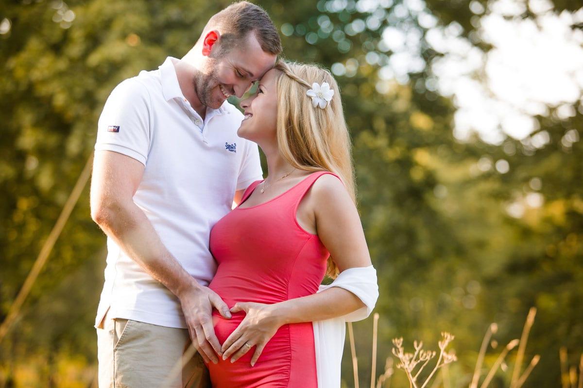 Mann und schwangere Frau kuessen sich beim Outdoor-Fotoshooting mit Donna Bellini Photo Studio Berlin