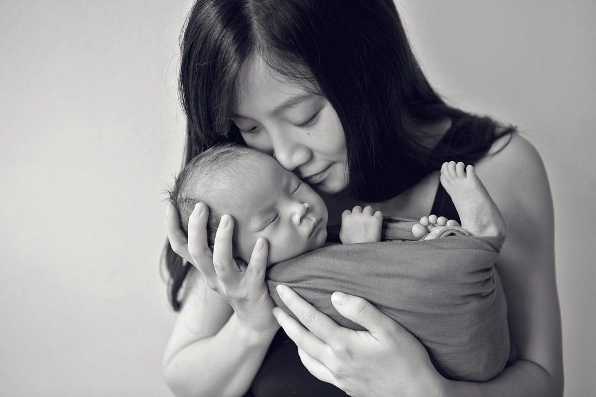 Mutter haelt ihr schlafendes neugeborenes Baby waehrend eines neugeborenen Fotoshootings in Donna Bellini Photo Studio Berlin