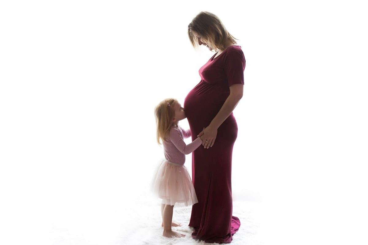 Schwangere Frau im roten Kleid mit kleinem Maedchen in einem Schwangerschaftsfotoshooting von Donna Bellini Berlin