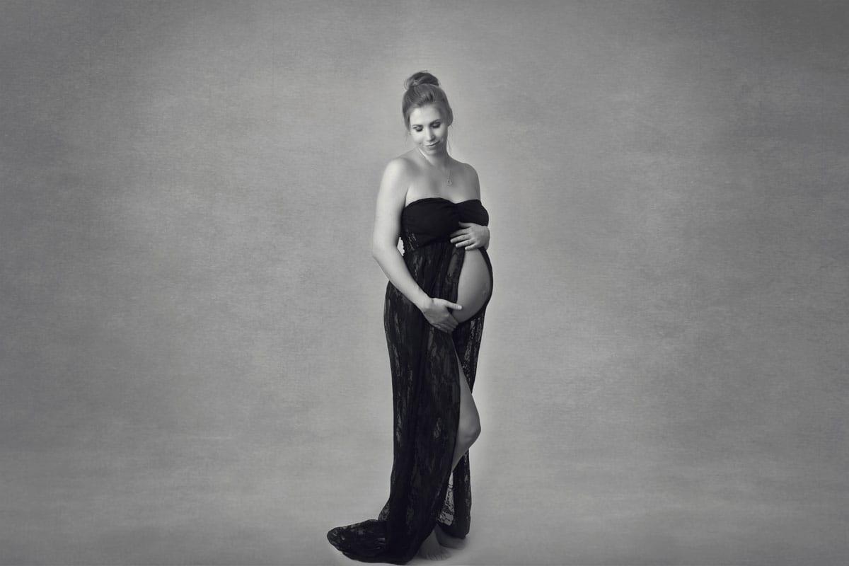 Schwangere Frau im schwarzen Kleid posiert bei einem Babybauch Fotoshooting von Donna Bellini Berlin