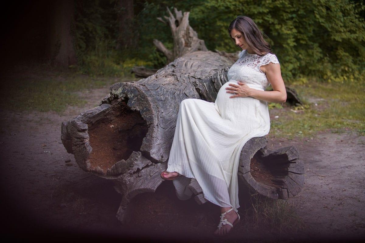 Schwangere Frau im weissen Kleid sitzt auf einem Holtzstamm und posiert waehrend Outdoor-Fotoshooting mit Donna Bellini Photo Studio Berlin