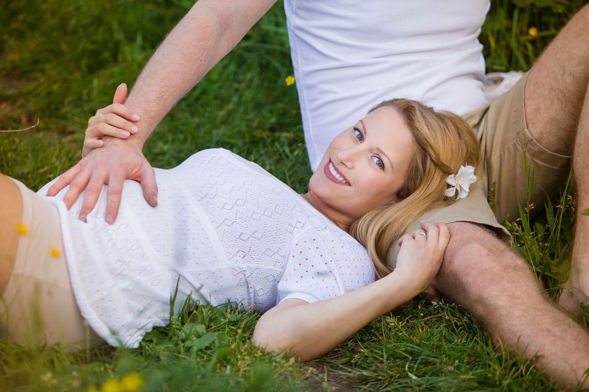 Schwangere Frau in der weissen Bluse legt auf Gras und posiert waehrend des Outdoor Fotoshooting im Donna Bellini Photo Studio Berlin auf