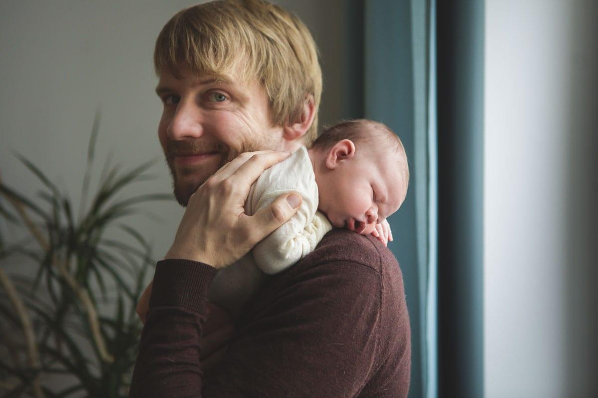 Vater haelt Neugeborenes auf der Schulter waehrend eines neugeborenen Fotoshootings im Donna Bellini Photo Studio Berlin