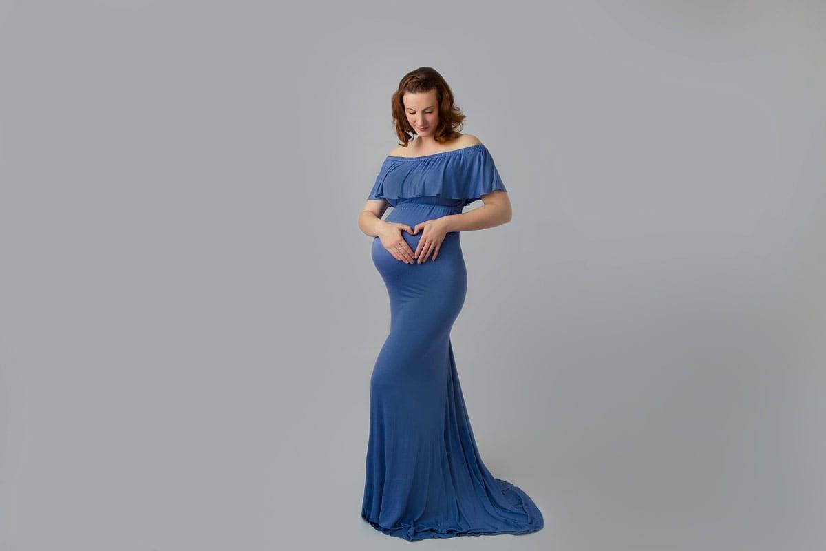 schwangere Frau posiert und macht ein Herz mit ihren Händen auf ihrem Babybauch waehrend eines Schwangerschafts-Fotoshootings im Donna Bellini Studio Berlin