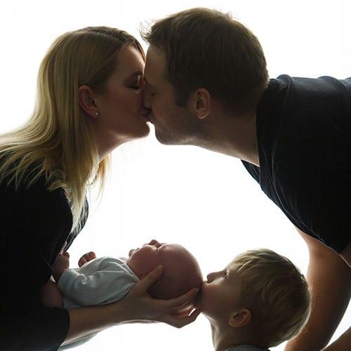 Donna-Bellini-Fotostudio-Berlin-fuer-Familienfotografie-Eltern-kleiner-Junge-und-Neugeborener-kuessen-sich.