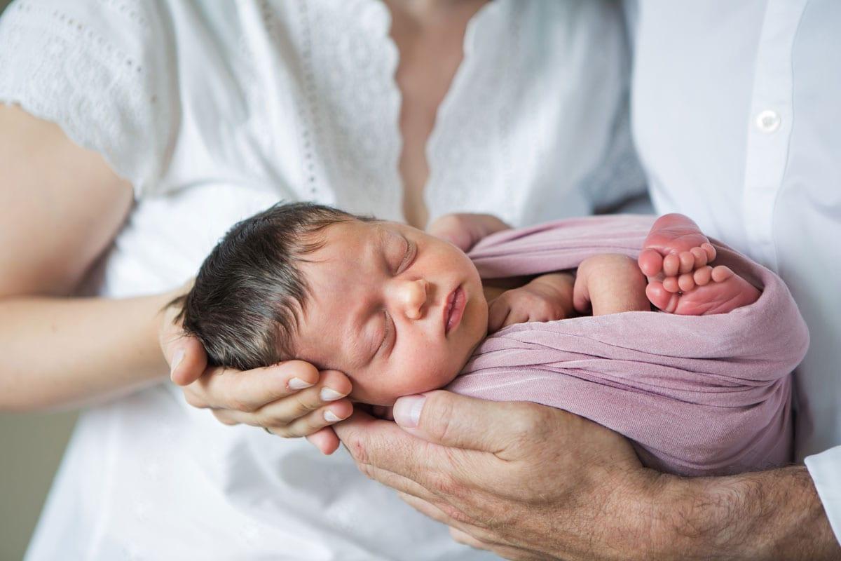 Neugeborene schlafen in Haenden der Eltern Newborn Shooting Berlin