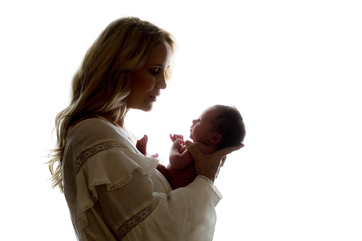 Newborn Shooting Berlin Mutter haelt Neugeborenen in Licht und Schatten