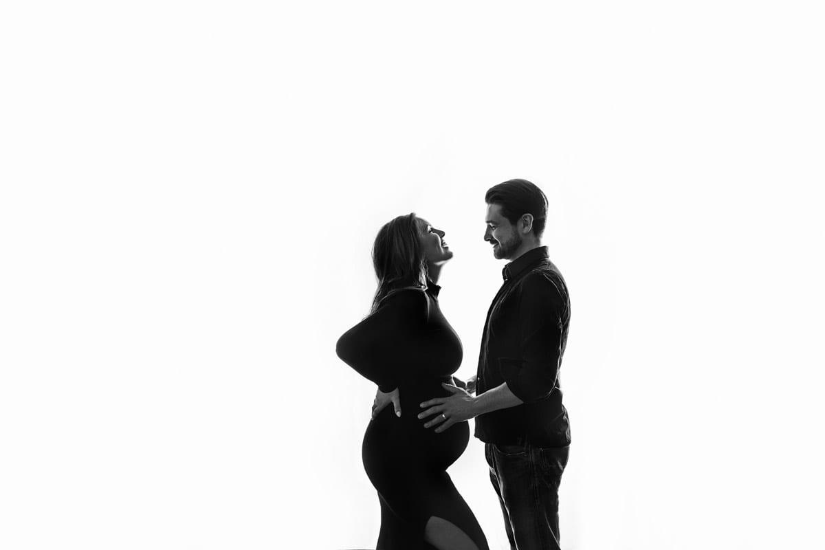 Paar posiert auf weissem Hintergrund waehrend Babybauch Shooting Berlin
