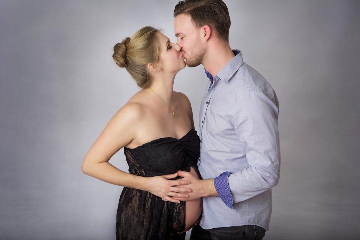 Schwangere und Partner kuessen sich beim Babybauch Shooting